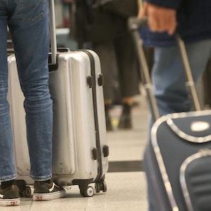 Passagiere stehen mit ihren Reise-Koffern am Flughafen Düsseldorf in einer Schlange, um für einen Eurowings-Flug nach Palma de Mallorca einzuchecken.