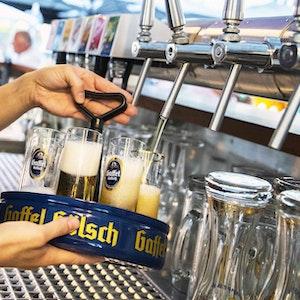 Eine Köbine zapft Gaffel-Kölsch in einem Biergarten.