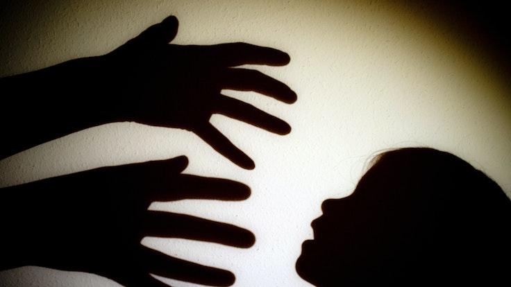 Schatten von Händen einer erwachsenen Person und dem Kopf eines Kindes an einer Wand eines Zimmers.