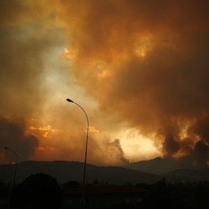 Dunkle Rauchwolken steigen 35 Kilometer entfernt von Athen in den Himmel, Grund dafür sind die anhaltenden Waldbrände.