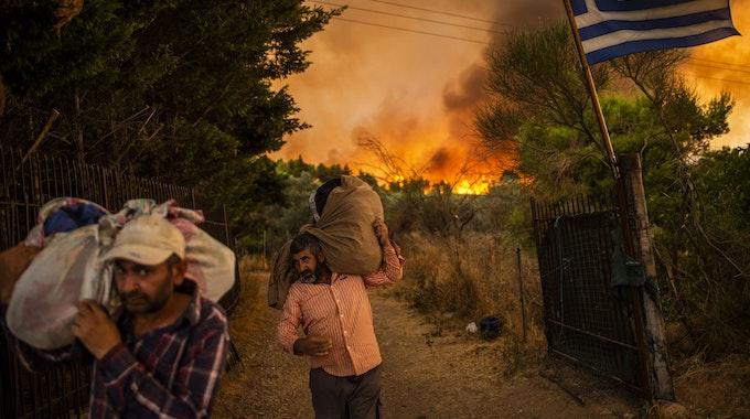 Menschen versuchen Teile ihrer Habe in Sicherheit zu bringen, während ein Waldbrand in einem Waldgebiet nördlich von Athen wütet.