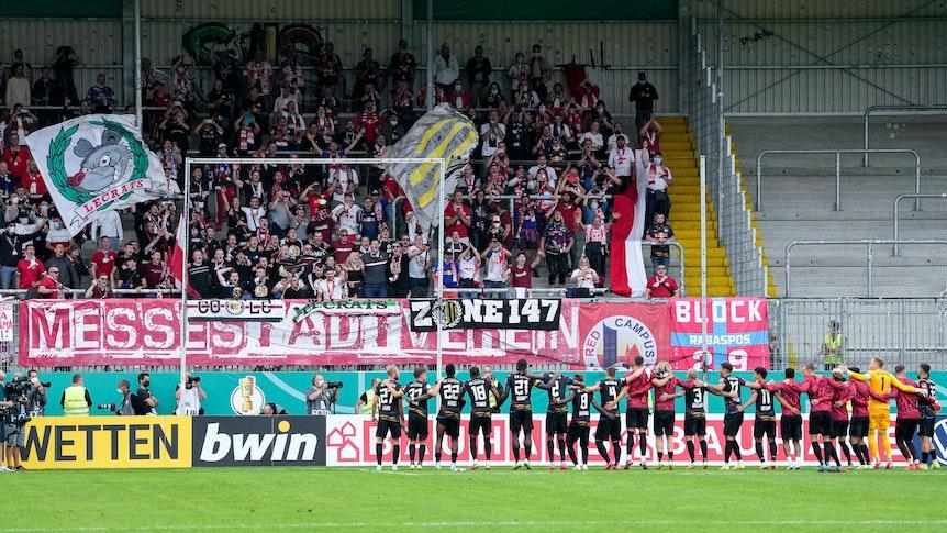 Die Spieler von RB Leipzig feiern vor dem eigenen Fanblock mit den mitgereisten Fans.