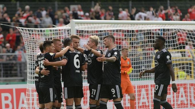 Die Spieler von Fortuna Düsseldorf bejubeln im DFB-Pokal in der Spielertraube ein Tor von Rouwen Hennings.