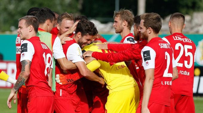 Die Spieler des 1. FC Köln umarmen Marvin Schwäbe.