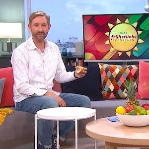 Daniel Boschmann sitzt mit Hotdog auf der Couch beim Sat.1 Frühstücksfernsehen, Moderatorin Karen Heinrichs hält lachend die Hände vors Gesicht.