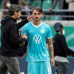 Wolfsburgs Trainer Mark van Bommel (l) steht vor der Einwechslung mit Maximilian Philipp zusammen.