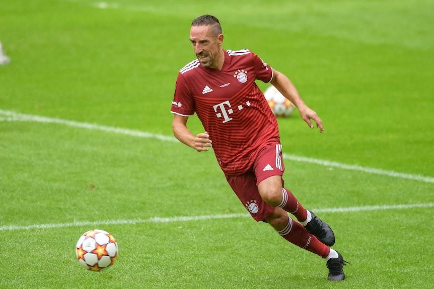 Franck Ribery indossa una maglia del Bayern Monaco con un calcio divertente all'Allianz Arena.