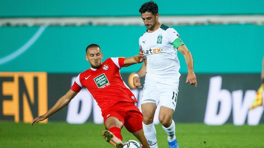 Rene Klingenburg (l.) vom 1.FC Kaiserslautern im Zweikampf mit Gladbachs Kapitän Lars Stindl (r.) beim Pokal-Duell am 9. August 2021 auf dem Betzenberg.