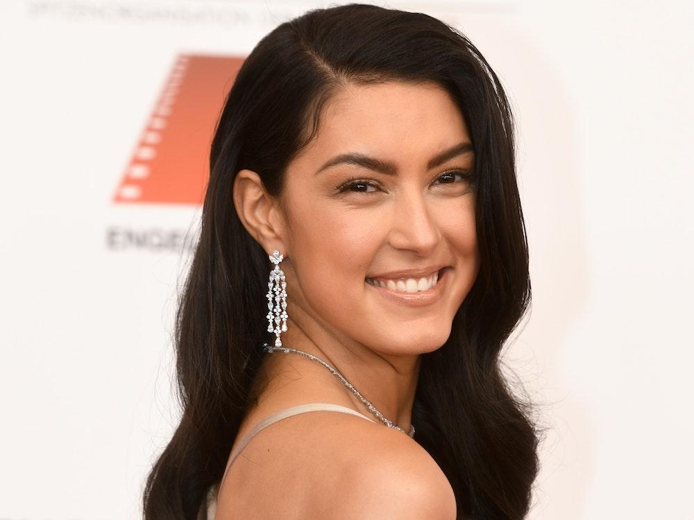 Rebecca Mir, Model, posiert beim 47. Deutschen Filmball ins Hotel Bayerischer Hof mit offenen Haaren in einem beigefarbenen Kleid.