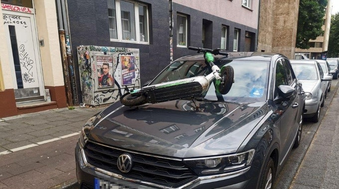 Ein E-Scooter liegt auf der Windschutzscheibe eines Autos.