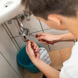 Handwerker arbeitet mit einer Zange an einem Wasserrohr. Foto von der dpa, honorarfrei