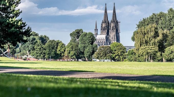 Wolkenbank und Sonnenschein im Kölner Rheinpark mit Blick auf den Dom.
