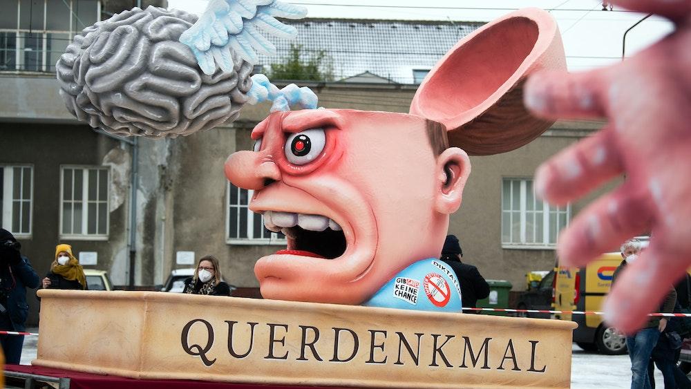 Ein Motto-Wagen mit einer Figur mit aufgeklapptem Schädel, darüber ein Gehirn mit Flügeln, und der Aufschrift Querdenkmal wird vor der Wagenbauhalle präsentiert. Die Düsseldorfer Karnevalisten wollen in der nächsten Saison nur Geimpfte und Genesene zu Feiern zulassen.