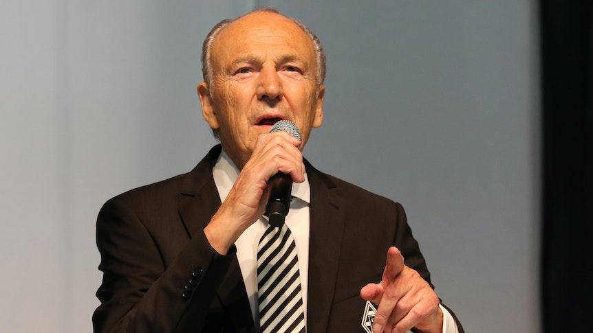 Borussias Präsident Rolf Königs bei der Mitgliederversammlung am 10. August 2021 im Gladbacher Stadion. Der 79-Jährige hält in der rechten Hand ein Mikro, mit der linken Hand deutet er in Richtung Zuhörer.