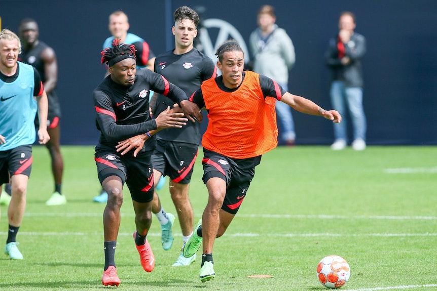 Yussuf Poulsen (r.) versucht im Training von RB Leipzig Mohamed Simakan abzuschütteln.
