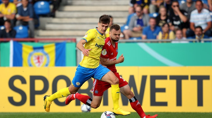 Im Spiel der ersten Runde des DFB-Pokals spielt Eintracht Braunschweigs Danilo Wiebe gegen Manuel Wintzheimer vom Hamburger SV den Ball.