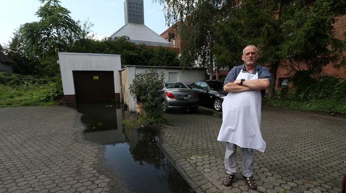 Konditormeister Udo Robl steht neben einer Pfütze und in seinem Geschäft Feine Torte in Niehl.