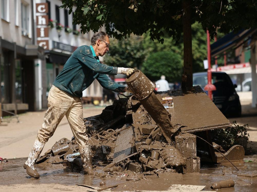 Das Foto zeigt einen Mann, der Schlammreste aus einem Haus auf einem Haufen von Schutt ausgießt.