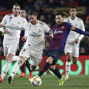 Real Madrids Sergio Ramos (M) und Lionel Messi (2.v.r.) vom FC Barcelona kämpfen um den Ball.
