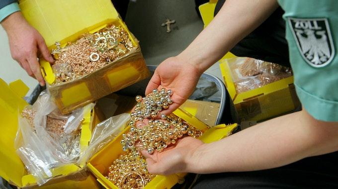 Zwei Zollbeamte zeigen geschmuggelten Goldschmuck aus einem Koffer.
