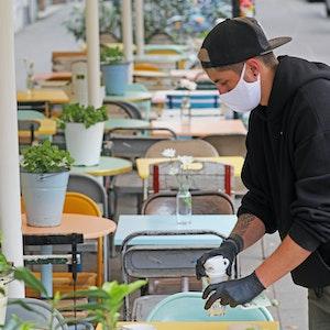 Ein Kellner räumt vor dem Kölner Lokal Herr Pimock einen Tisch ab.