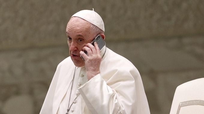 Papst Franziskus spricht am Ende seiner wöchentlichen Generalaudienz in der Halle Paul VI. in ein Telefon.