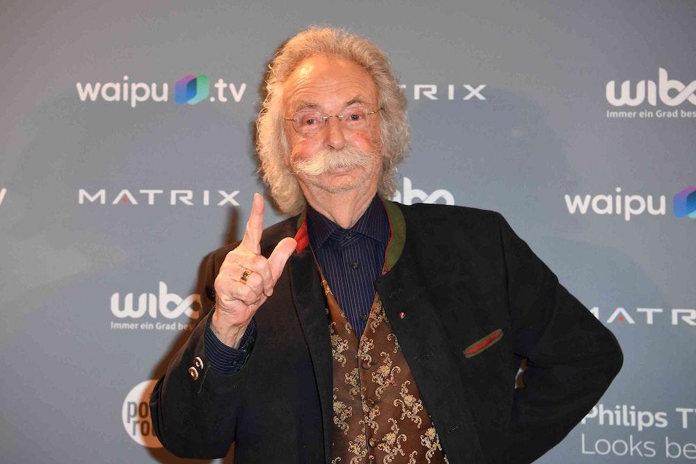 Jean Pütz steht vor einer Fotowand im Hotel Adlon.
