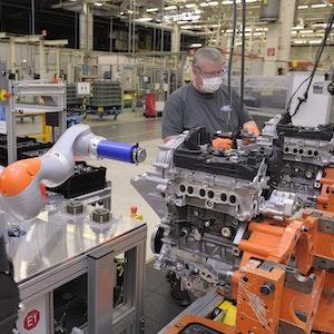 Ein Roboter arbeitet bei Ford mit einem Mitarbeiter zusammen an einem Motorblock.