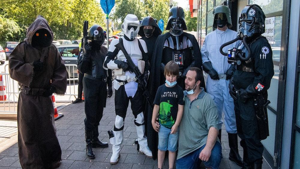 Philipp Oszcera und sein Sohn Luke lassen sich von seiner Frau Nadine mit Darstellern in Kostümen aus der Filmreihe Star Wars vor dem Duisburger Impf-Zentrum fotografieren.