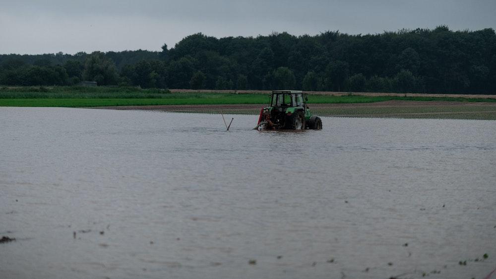 Ein Traktor steht auf einem gefluteten Feld bei Heimerzheim.