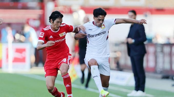Nadiem Amiri von Bayer Leverkusen im Laufduell mit Genki Haraguchi von Union Berlin.