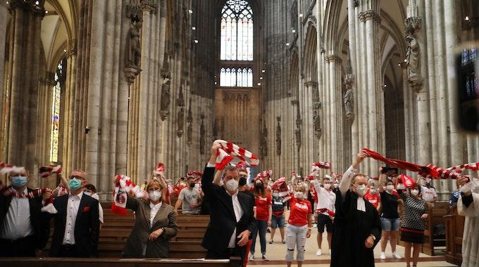 Fans des 1. FC Köln schwenken ihre Schals im Kölner Dom.