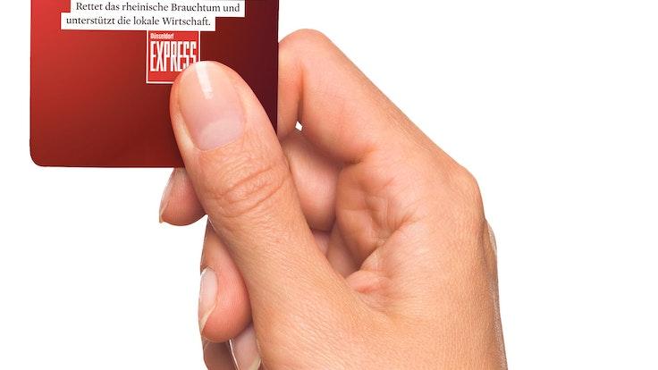 Eine Hand hält den Brauchtums-Pass für Düsseldorf.