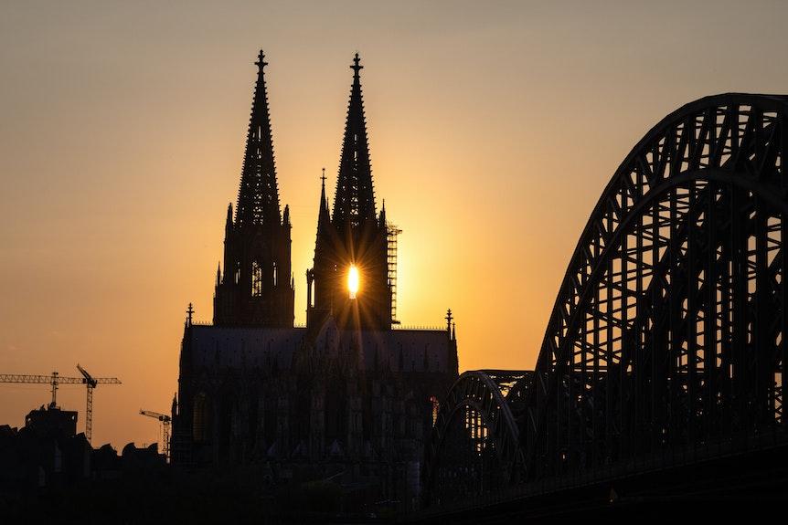 Die Sonne geht hinter dem Kölner Dom (Hohe Domkirche St. Petrus) unter.