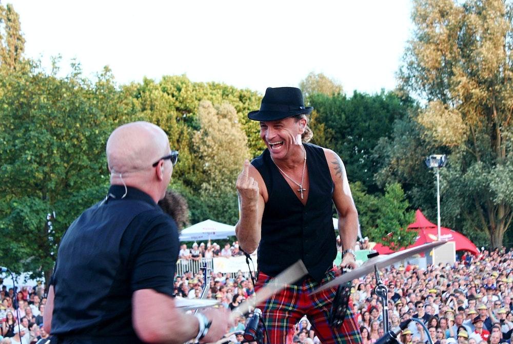 Kölschrocker Peter Brings (r.) zeigt Schlagzeuger Christian Blüm bei einem Konzert den Mittelfinger.