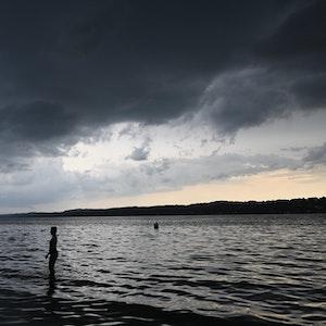 Dunkle Wolken hängen am Sonntag (15. August) über dem Starnberger See. In Teilen Bayerns gab es am Sonntag (15. August) erneut heftige Schauer und Gewitter.