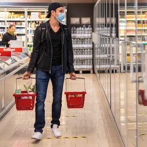 Ein Kunde geht in einem Supermarkt einkaufen und trägt dabei einen Mundschutz.