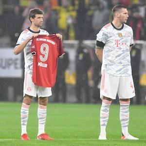 Thomas Müller hält ein Trikot in die Luft
