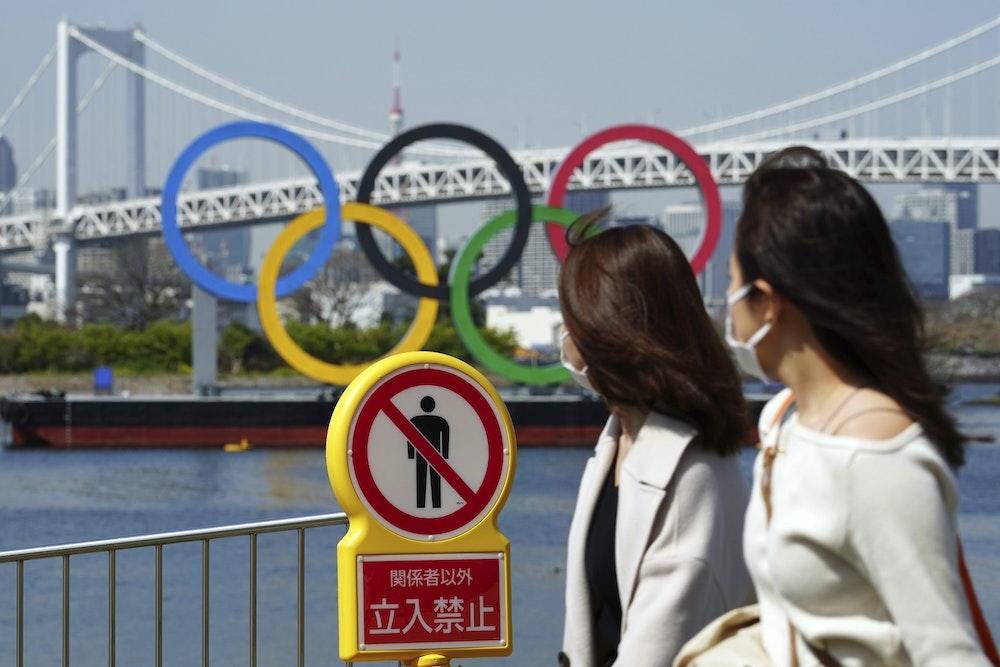 """Zwei Frauen gehen an einem """"Betreten verboten""""-Schild vorbei. Dahinter sind die Olympischen Ringe zu sehen."""