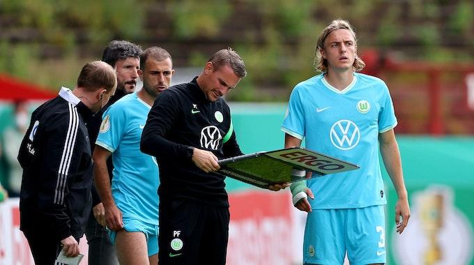 Die Wolfsburger Sebastiaan Bornauw und Admir Mehmedi machen sich im DFB-Pokal bereit für ihre Einwechslung.