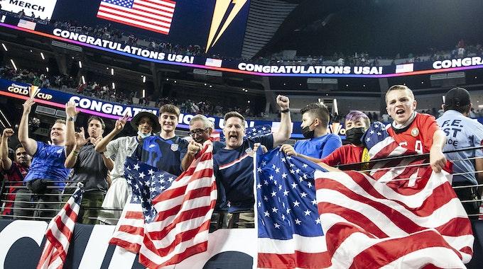 Fußballfans jubeln und schwenken US-amerikanische Flaggen.
