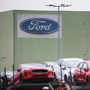 Neu gebaute Autos stehen auf Lastwagen vor dem Ford Werk.
