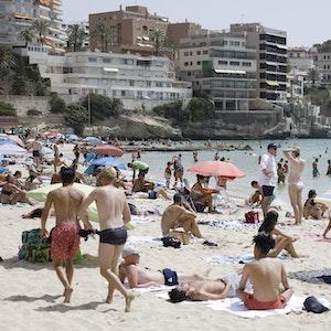 Einheimische und Touristen kühlen sich im Meer am Strand Cala Major in Palma de Mallorca ab.