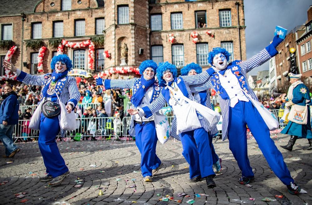 Karnevalisten einer Fußgruppe feiern beim Rosenmontagszug.