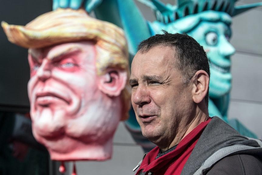 Wagenbauer Jacques Tilly steht in Düsseldorf vor seinen Karnevalswagen, die die Köpfe von US-Präsident Trump und die Freiheitsstatue zeigen.