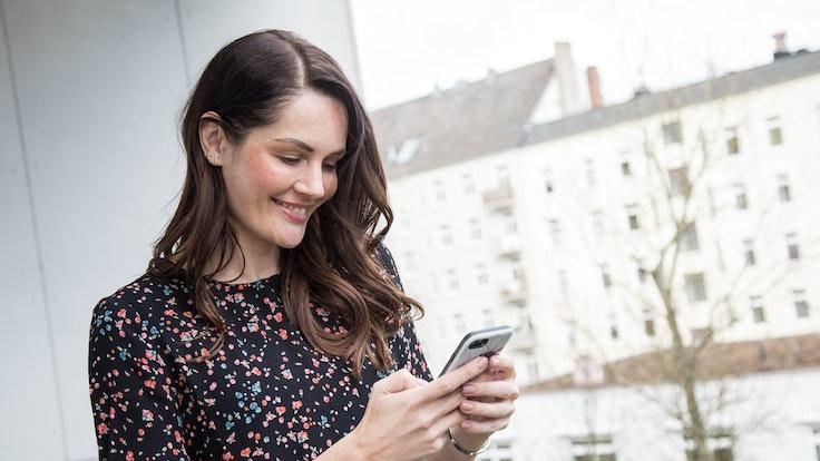 Eine Frau hält ein Smartphone in der Hand und lehnt an einem Balkon
