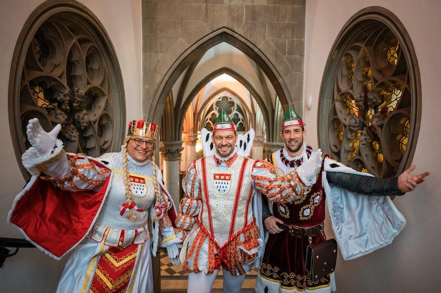 Jungfrau Gerdemie (Björn Braun, l-r), Prinz Sven I. (Sven Oleff) und Bauer Gereon (Gereon Glasemacher), das Kölner Dreigestirn, stehen auf einer Treppe im The Qvest Hotel.