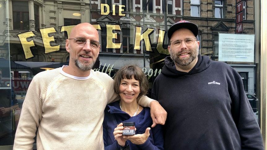 """Walter Schnerring, Andrea Bratu und Martin Block stehen vor ihrem Burgerladen """"Die fette Kuh""""."""