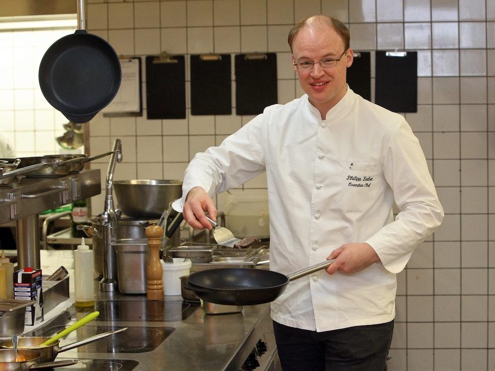 Philipp Ferber steht in der Küche und hält eine Pfanne in der Hand.