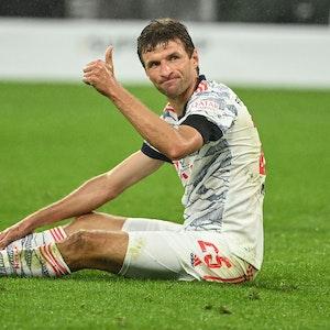 Thomas Müller sitzt auf dem Rasen und reckt den Daumen nach oben.